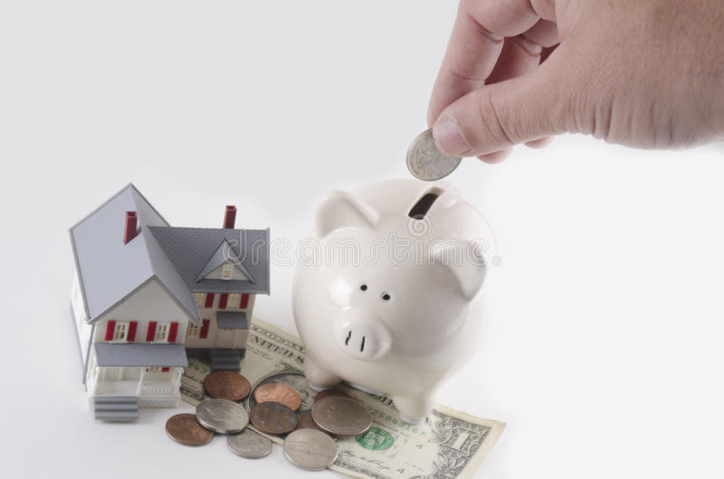 Mortgage Savings. A metaphor of a savings account or mortgage or loan payment plan. Shallow depth of field. Focus on the money being dropped in piggy bank stock photography