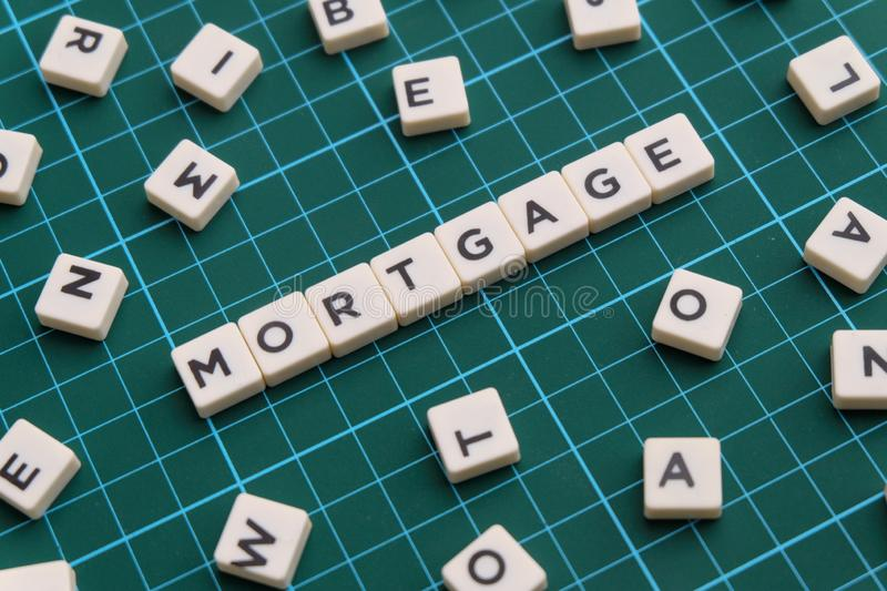 Mortgage word made of square letter word on green square mat background. Mortgage word made of square letter word on green square mat background royalty free stock photography