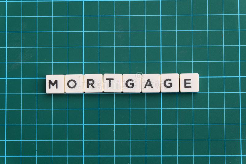 Mortgage word made of square letter word on green square mat background. Mortgage word made of square letter word on green square mat background royalty free stock photo