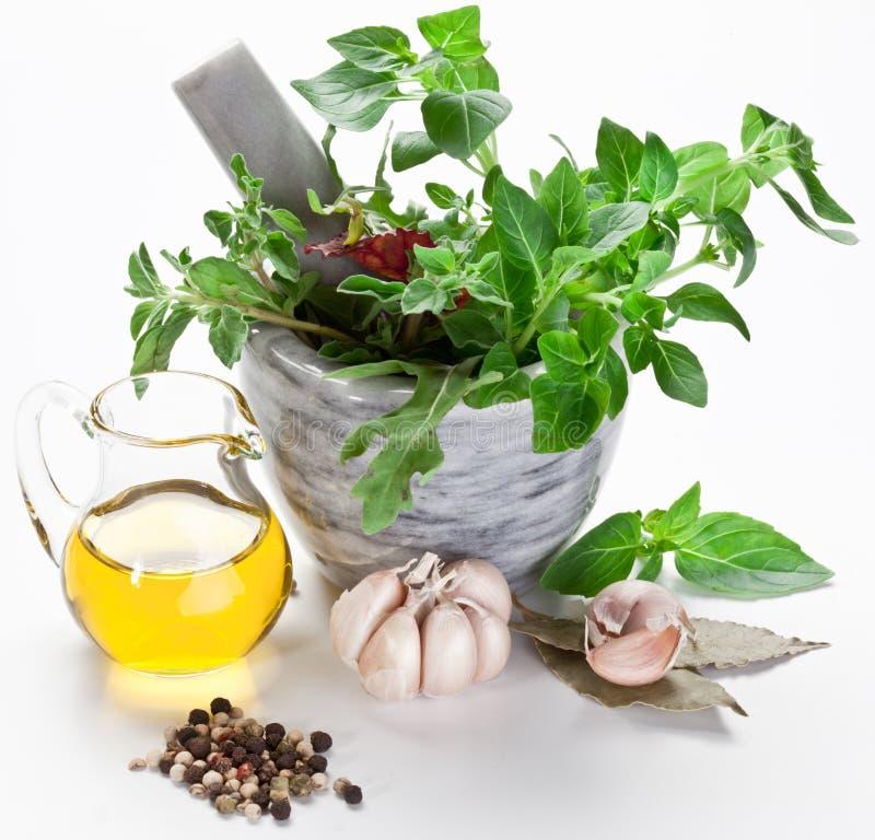 Mortier avec les herbes de pilon et de basilic et l'huile d'olive. photo stock