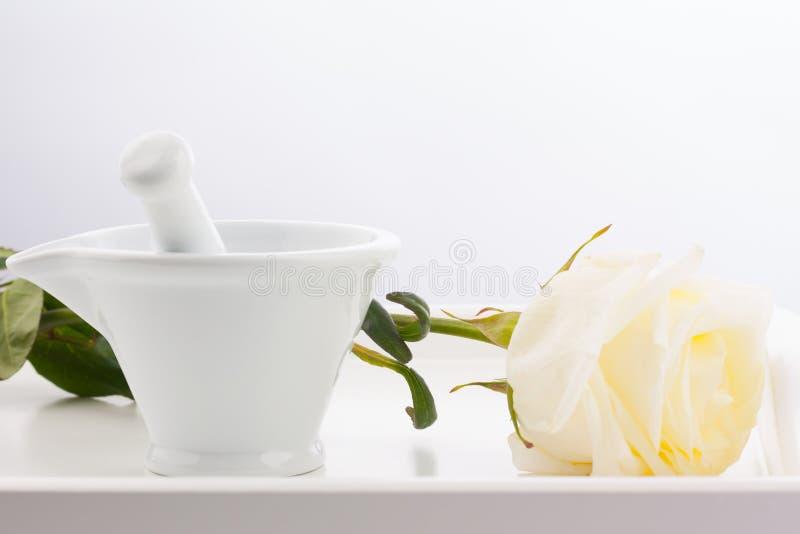 Mortier blanc, pilons et fleur rose blanche sur le plateau en bois d'isolement sur le fond blanc photo libre de droits