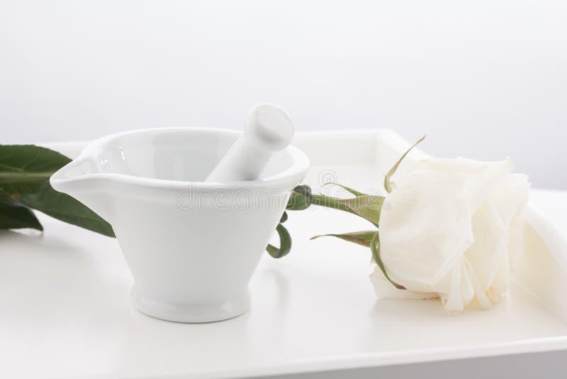 Mortier blanc, pilons et fleur rose blanche sur le plateau en bois d'isolement sur le fond blanc image stock