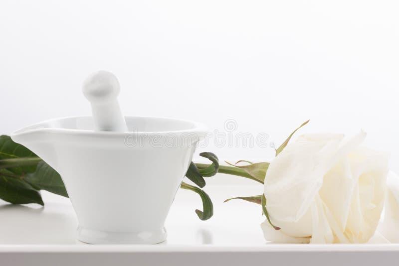 Mortier blanc, pilons et fleur rose blanche sur le plateau en bois d'isolement sur le fond blanc photos stock