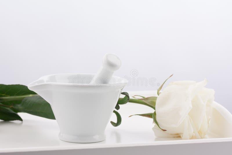 Mortier blanc, pilons et fleur rose blanche sur le plateau en bois d'isolement sur le fond blanc photos libres de droits