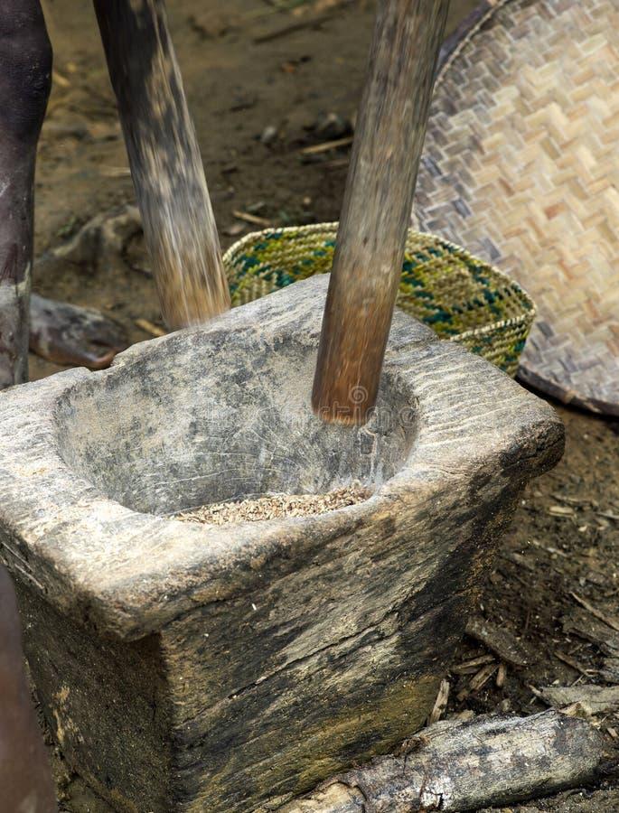 Mortier en pierre et pilon en bois pour le riz de broyage photo stock