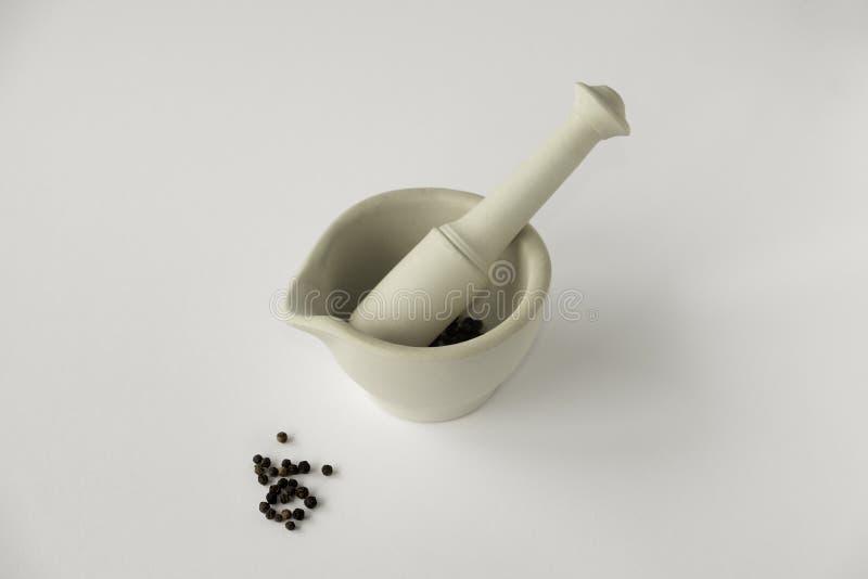 Mortier et pilon avec les grains de poivre noirs sur le backgrou blanc simple photo libre de droits