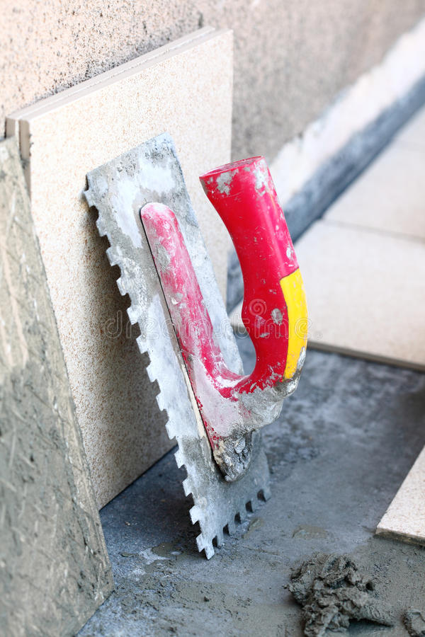 Mortier sur la truelle entaillée par construction de mur image stock
