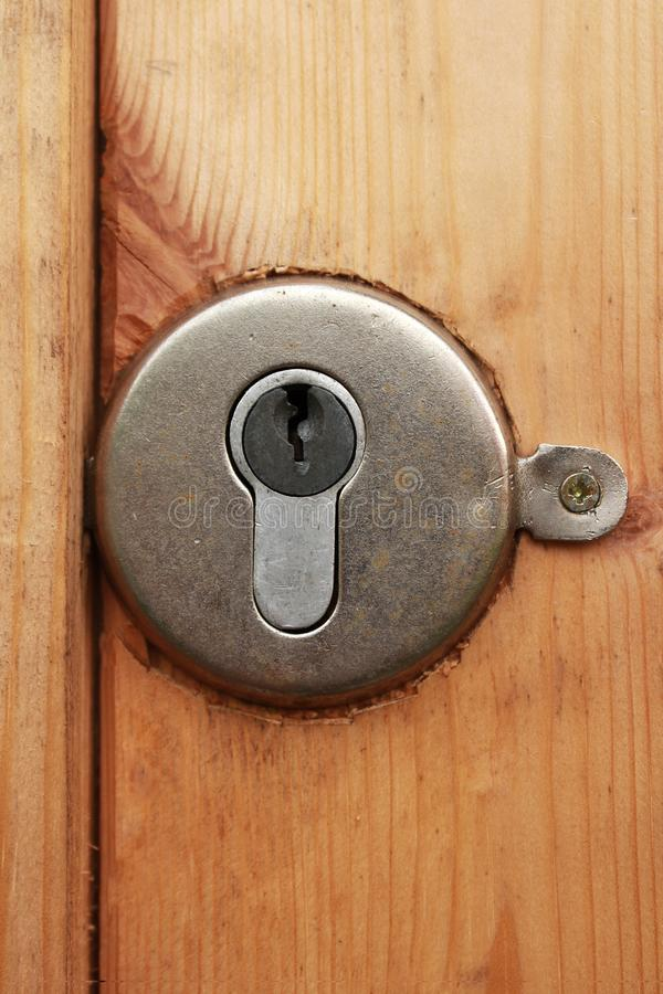 Mortise lock with keyhole embedded in a wooden door. Mortise round lock with keyhole embedded in a wooden door stock photography