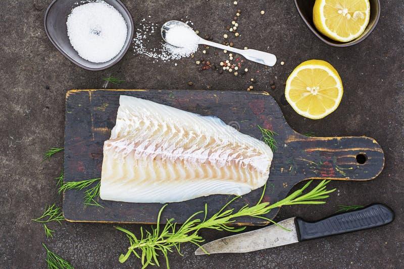 Morue crue avant la cuisson sur un hachoir noir avec les herbes et le sel de mer sur un fond foncé Vue supérieure photographie stock libre de droits