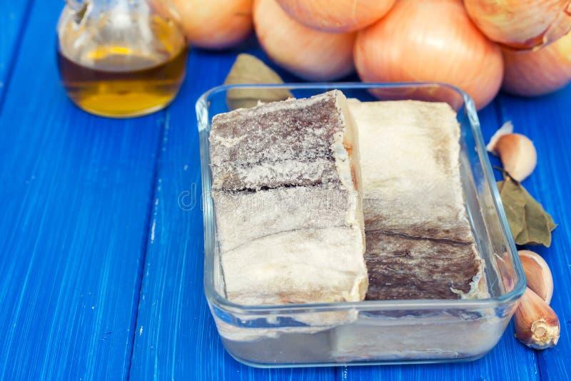 Morues sèches salées avec le pétrole, l'ail et l'oignon photo stock