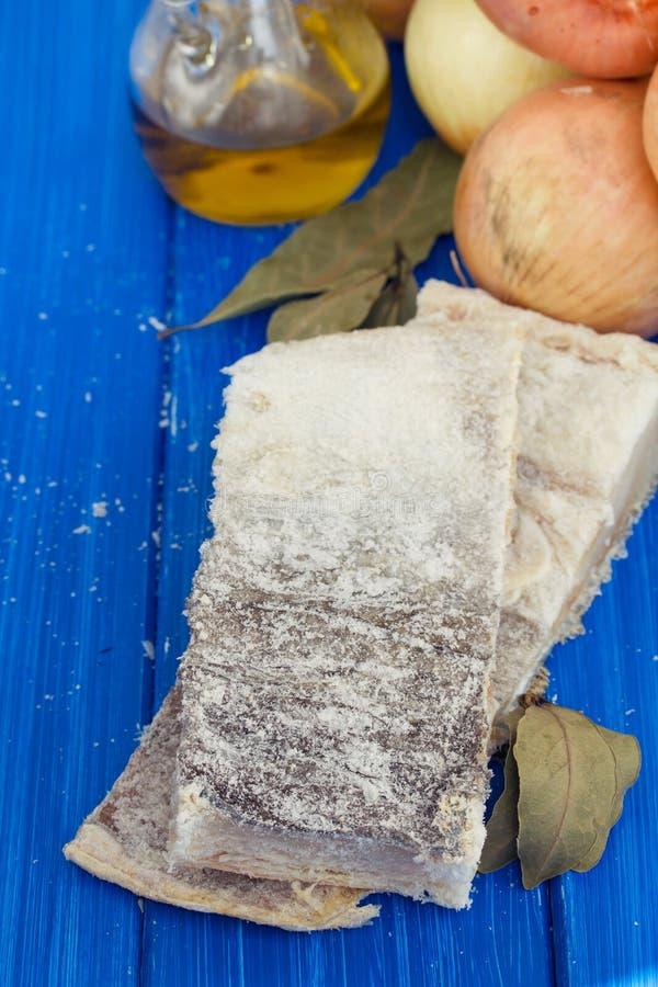 Morues sèches salées avec le pétrole, l'ail et l'oignon sur le fond en bois image libre de droits