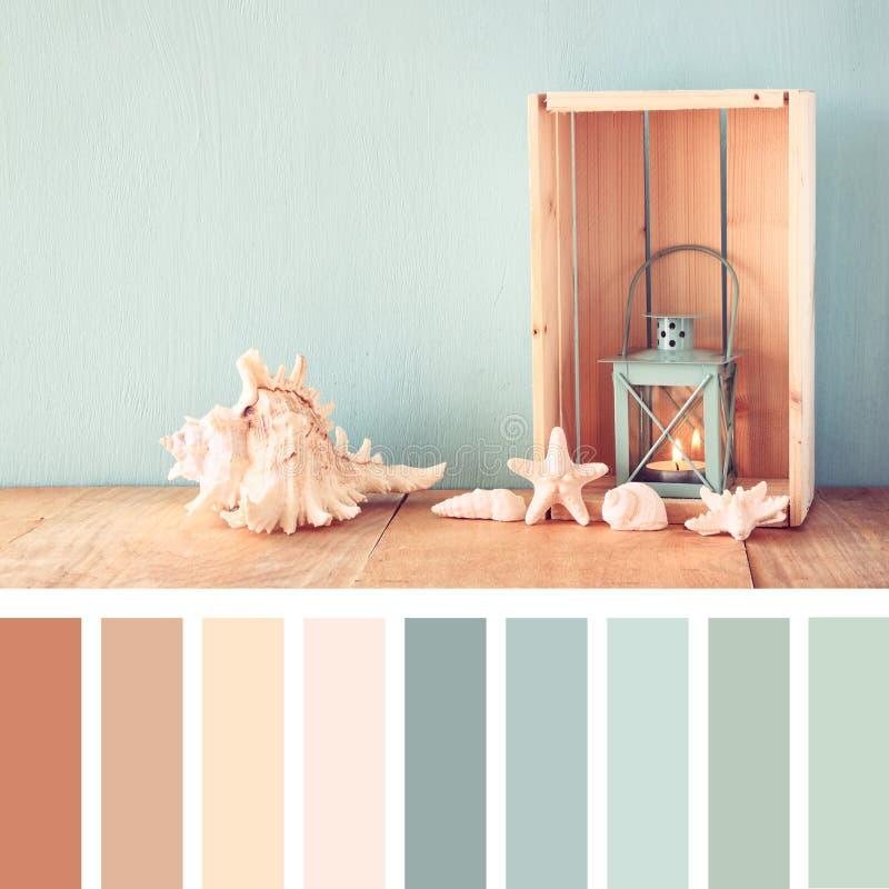 Morze lampion na drewnianym stole i skorupy rocznik filtrujący wizerunek nautyczny stylu życia pojęcie z paleta koloru swatches obraz stock