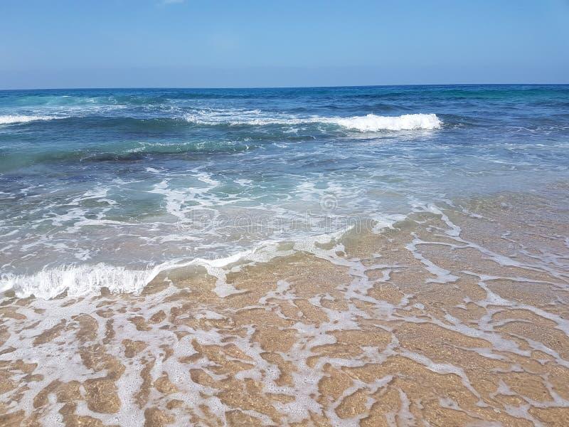 Morze plaża z małymi fala i niebieskim niebem zdjęcia stock