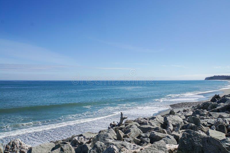 Morze popiół przy rockowym brzeg w Nowa Zelandia z jaskrawym niebieskim niebem i fala obrazy royalty free