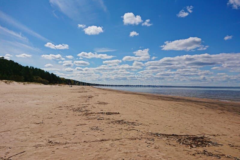 Morze z długą piaskowatą linią brzegową i niebieskim niebem z chmurami obraz royalty free