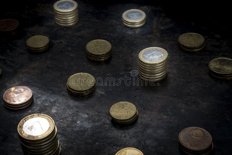 Mosaïque avec un motif régulier constitué de pièces en euros sur fond noir foncé en métal photo libre de droits