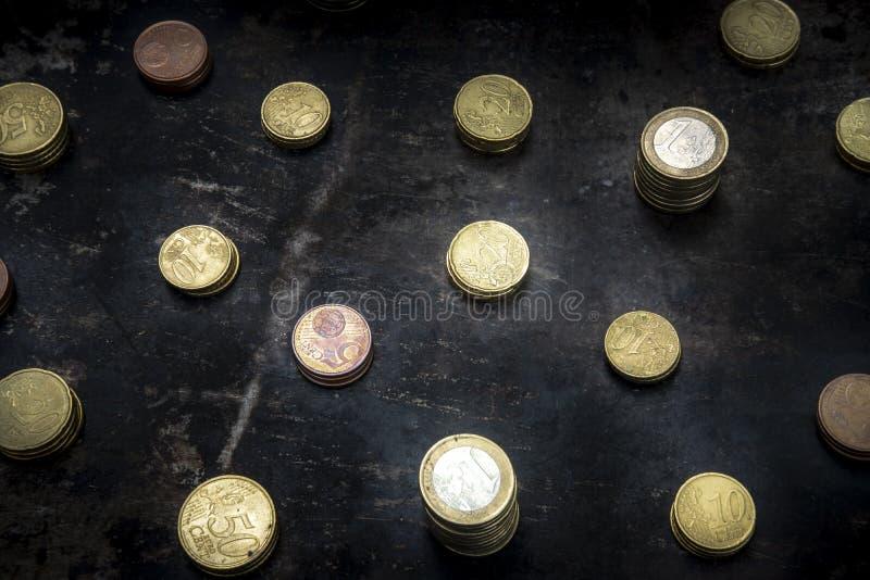 Mosaïque avec un motif régulier constitué de pièces en euros sur fond noir avec métal arraché images libres de droits