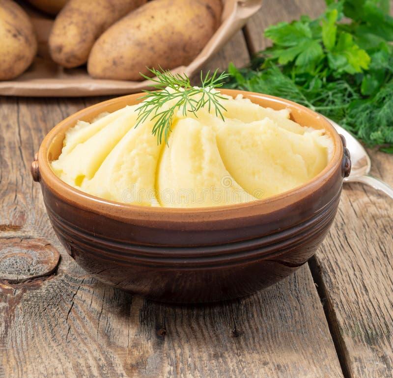Mosade potatisar, kokaad puré i brun bunke på mörk trälantlig bakgrund, sidosikt arkivbilder