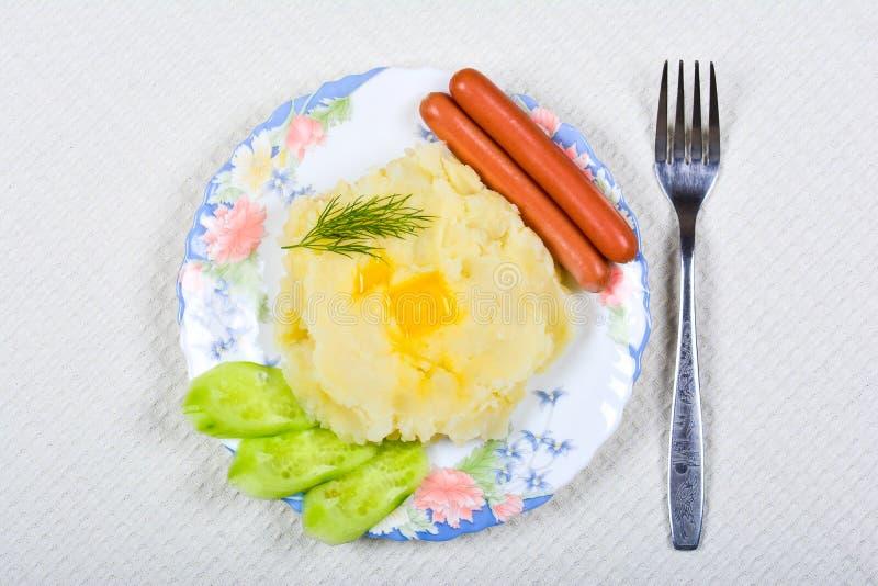 Mosade potatisar med korvar fotografering för bildbyråer