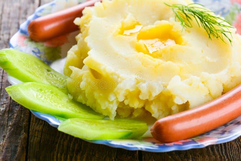 Mosade potatisar med korvar royaltyfri fotografi
