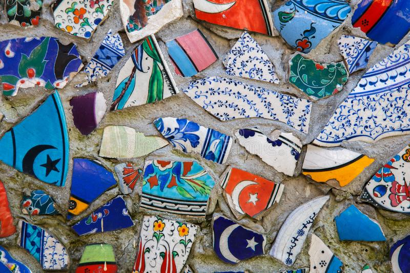 Mosaic of broken tiles wall in Istanbul, wall made of colorful mosaic broken tiles Turkey. Splinters of a white ceramic. Tile on cement. Texture pieces against stock image