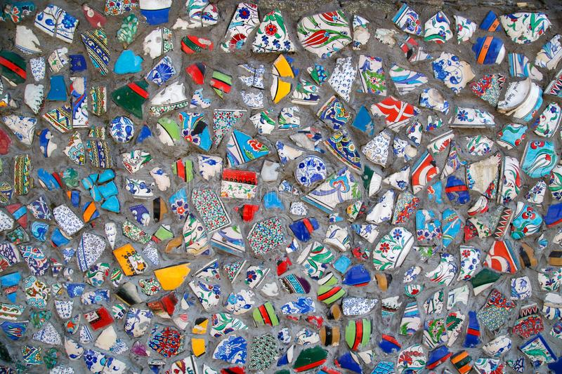Mosaic of broken tiles wall in Istanbul, wall made of colorful mosaic broken tiles Turkey. Splinters of a white ceramic. Tile on cement. Texture pieces against royalty free stock photo