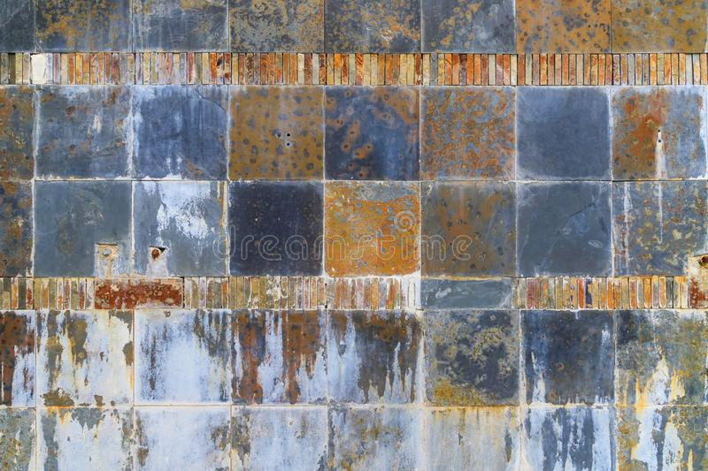 Mosaic of grey and yellow tiles in geometric pattern with rust. stock images
