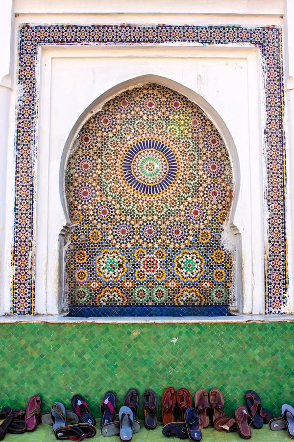 Mosaic niche in a mosque in the foreground deferred shoes,. Mosaic niche in a mosque in the foreground many deferred shoes stock photos