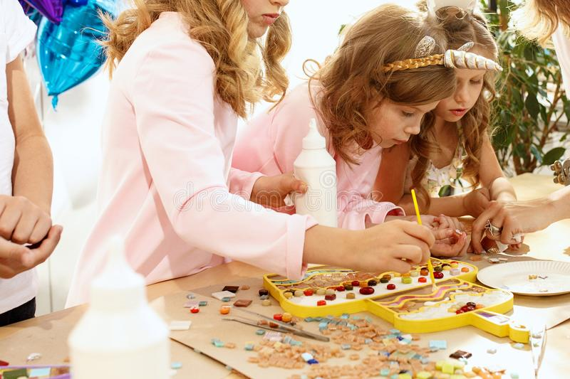 Mosaic puzzle art for kids, children`s creative game. The mosaic puzzle art for kids, children`s creative game. The hands are playing mosaic at table. Colorful royalty free stock photography