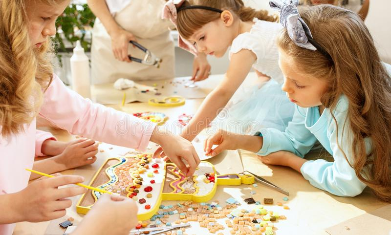 Mosaic puzzle art for kids, children`s creative game. The mosaic puzzle art for kids, children`s creative game. The hands are playing mosaic at table. Colorful stock photography