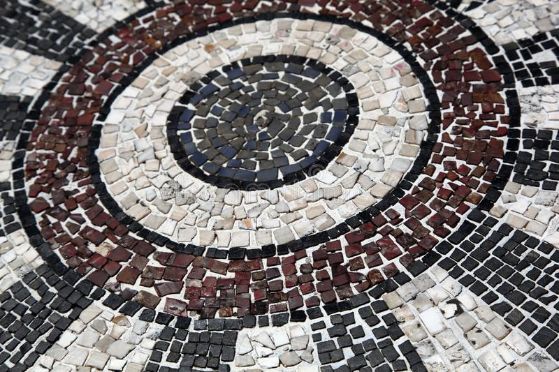 Mosaic stone floor in a circular pattern. Mosaic stone floor in a beautiful circular pattern in black, white and red royalty free stock image