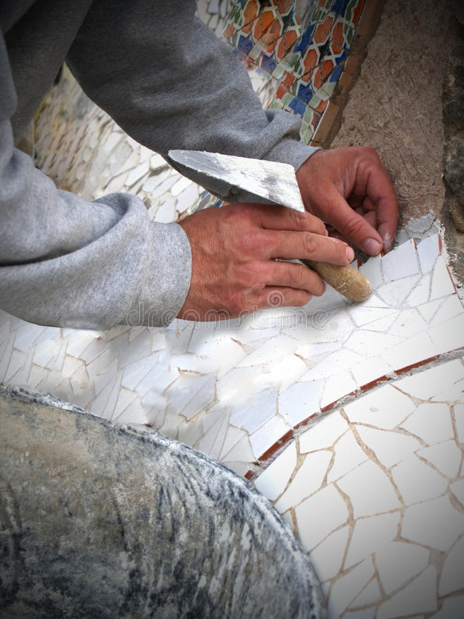 Mosaic Worker lays tiles stock photo
