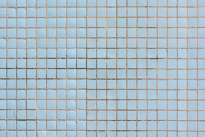 Mosaik av små keramiska fyrkanter Töm blå bakgrund arkivfoton