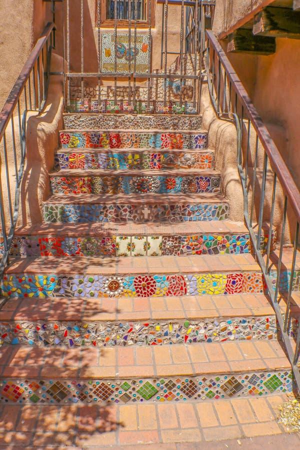Mosaik- und Fliesenschritte, die von der Straße zu einem Eisentor führen stockfoto