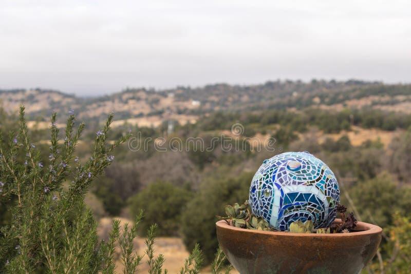 Mosaikgartenball in den mehrfarbigen Schatten des Blaus gemacht von den Buntglasfliesen, Hügel und Berge gestalten im Hintergrund stockbilder