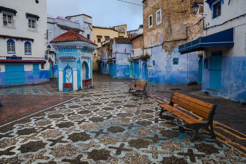Mosaikquadrat mit Bänke und ein kleiner Pavillon in einer blauen Stadt stockfoto