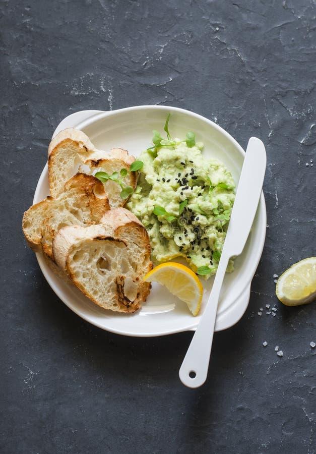 Mosat avokadorostat brödbröd på en grå bakgrund, bästa sikt sund frukost arkivbilder