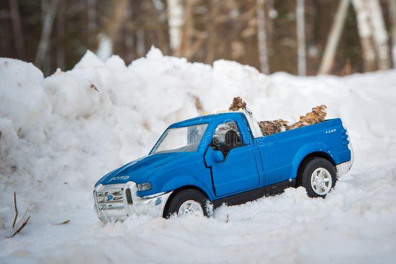moscú En diciembre de 2018 Camioneta pickup azul Ford F350 del juguete en conos de abeto del bosque de la nieve que llevan Camino imagenes de archivo