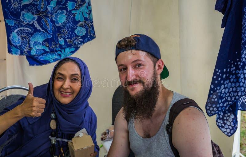 Moscú, parque en Krasnaya Presnya, el 5 de agosto de 2018: Retrato de un hombre joven con una barba y de una mujer de Indonesia E fotografía de archivo