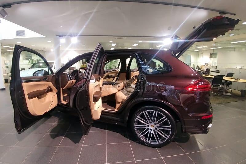 Moscú, Rusia - 1 de abril de 2019: Brown Porsche Cayenne Turbo, SUV superior en la sala de exposición con las puertas abiertas y  imagen de archivo