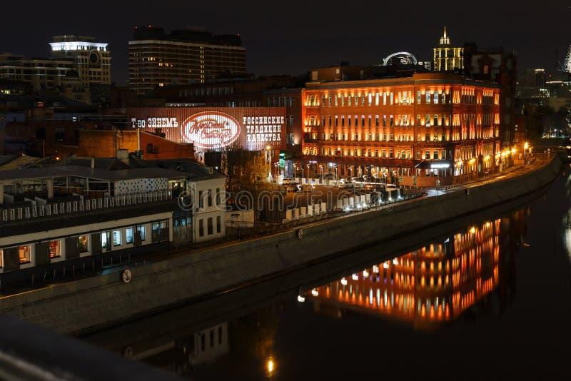 Moscú, Rusia - 26 de abril de 2018: Edificios de la fábrica octubre rojo del chocolate en el fondo del río de Moskva en la noche imagenes de archivo