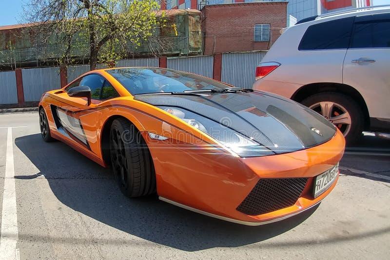 Moscú, Rusia - 14 de abril de 2019: Lamborghini Gallardo anaranjado brillante con la capilla del carbono y otras piezas parqueada fotografía de archivo libre de regalías