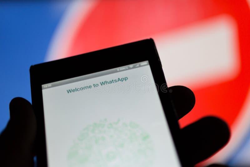 MOSCÚ, RUSIA - 16 DE ABRIL DE 2018: Teléfono móvil con el uso de Whatsapp a disposición contra una muestra que prohíbe foto de archivo