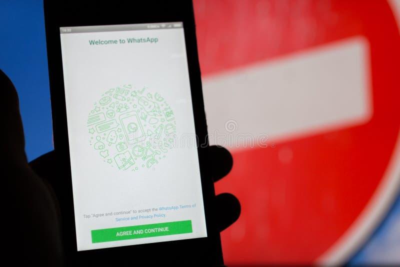 MOSCÚ, RUSIA - 16 DE ABRIL DE 2018: Teléfono móvil con el uso de Whatsapp a disposición contra una muestra que prohíbe fotografía de archivo libre de regalías