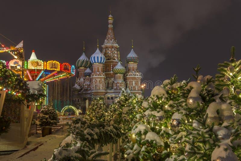 Moscú, Rusia 22 de diciembre de 2018 Mercado de la Navidad en la Plaza Roja, carrusel en la noche nevosa imagen de archivo