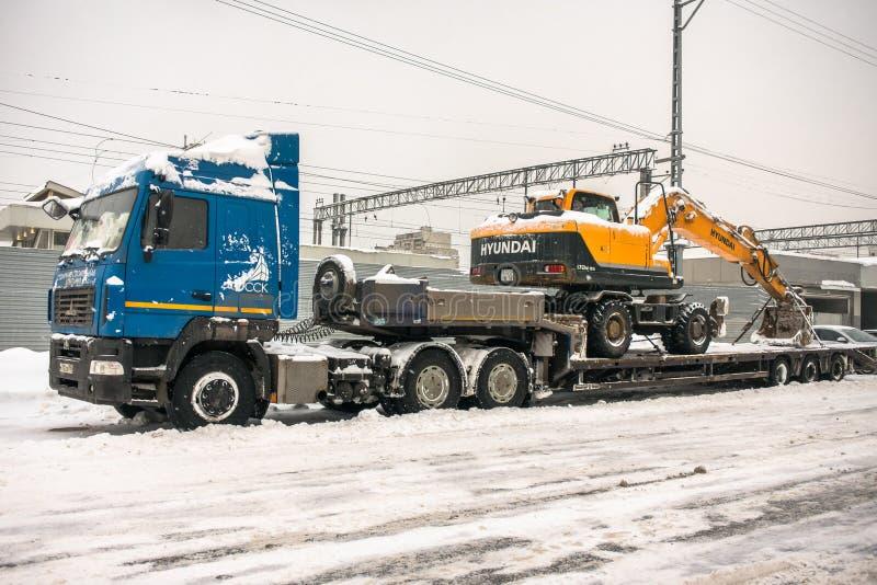 MOSCÚ, RUSIA - 5 DE FEBRERO DE 2018: El camión potente especializado transporta el excavador amarillo Hyundai de la rueda en un r fotografía de archivo libre de regalías