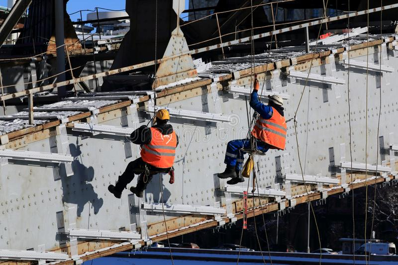 Moscú, Rusia - 14 de febrero de 2019: Los trabajadores realizan el trabajo en la mucha altitud sobre el río de Moscú fotos de archivo libres de regalías