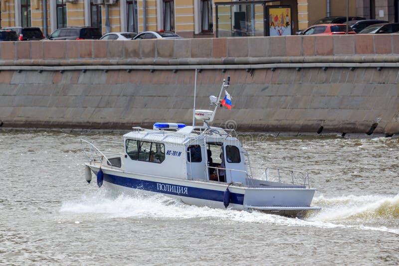 Moscú, Rusia - 21 de junio de 2018: Barco de policía que acomete a lo largo de superficie del agua en un fondo del terraplén del  fotos de archivo libres de regalías