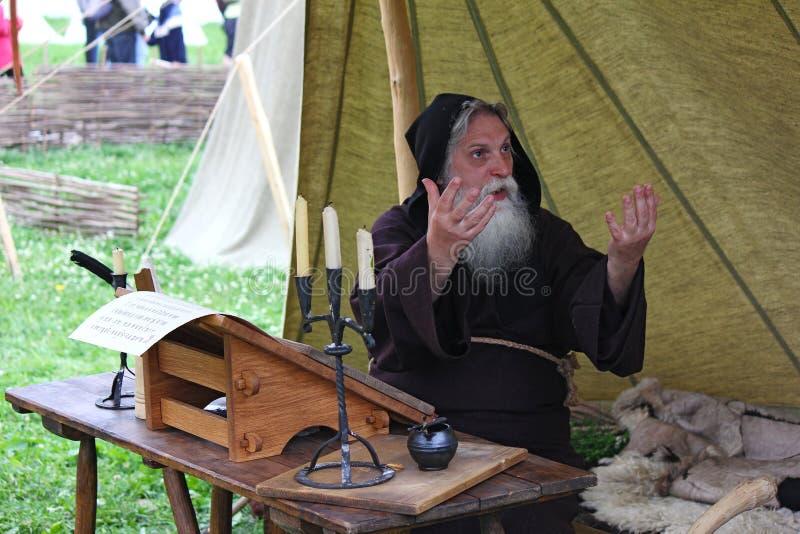 MOSCÚ, RUSIA - 22 DE JUNIO DE 2013: Escribano medieval del monje en el escritorio imagen de archivo libre de regalías