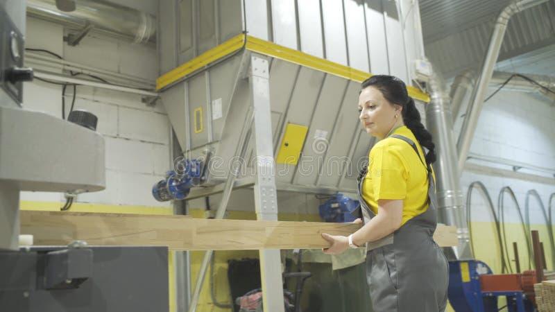 Moscú, Rusia - 15 de junio de 2018: El trabajador pone al tablero de madera en máquina acci?n El trabajador de mujer coge fácilme imagenes de archivo